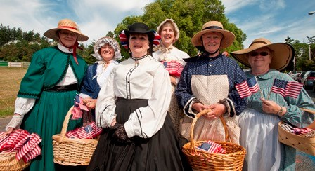 Volunteers dressed in period clothing gather for the 4th of july parade