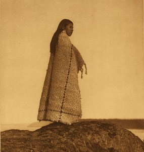 A Cowichan girl standing on a rock.