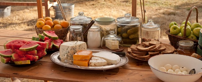 Food options for reenactors including a cheese platter, watermelon, oranges, pickles, bread, apples, and eggs.