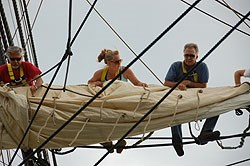 Volunteers furling a sail on Friendship