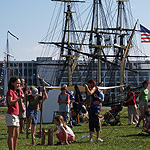 Adults and children engaged in various activities with three-masted tall ship in background.