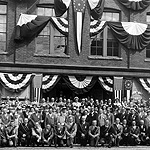 Historic black and white photo of many people gathered in front of a brick building decorated with bunting.