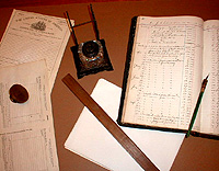 inkwells, ledger books, pens, and paper spread out on a desk in the Custom House.