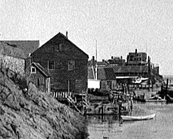 An historic photograph of Pedrick Store House in its original place on Tucker's wharf