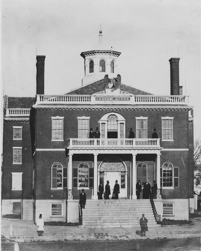 historical black and white photo of men standing in front of building