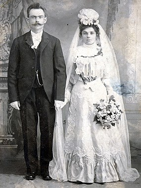 wedding portrait; groom is wearing a suit and bride is wearing a floor length gown with a long veil.