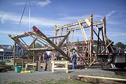 timber frames being raised into place