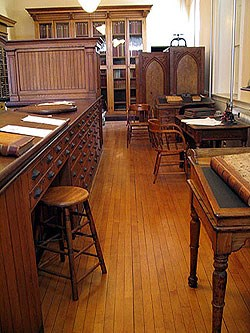 behind the desk in the Custom House Public Office are desks and filing cabinets