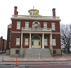 The Custom House is a large, square two story building with a cupola in the middle of the roof and a large portico over the grand stairs that sweep up to the front door.