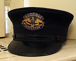 a customs inspector's hat has a gold badge with an eagle and the words