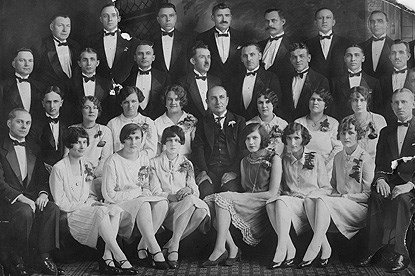 A group of men and women in tuxedos and gowns in a formal portrait