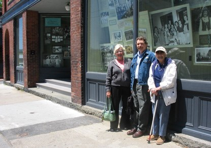 three people in front of a storefront exhibit