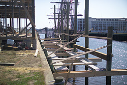 horizontal timbers are attached to pilings driven into the harbor floor next to Derby Wharf.
