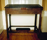 a tall wooden desk with an angled top for writing