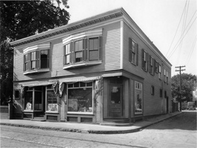 A two story building with bay windows on the second floor and storefronts on the first floor.