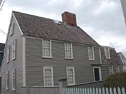 The Narbonne House is a two story grey house. On the left of the center chimney is a peaked roof, and on the right is a lower barn like, or gambrel roof.
