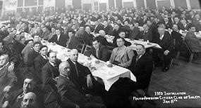 Rows of men sitting at tables at a formal banquet