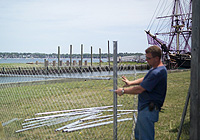 A workman assembles fencing on Central Wharf, with the replica tall ship Friendship in the background