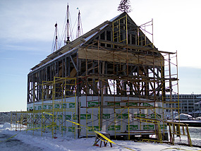 the skeleton of Pedrick Store House being wrapped for protection from the elements