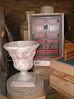 A large alabaster urn sits next to a red and black lacquered Chinese cabinet