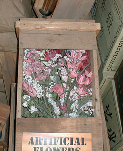 artificial flowers of pink, red, and white in a shipping crate
