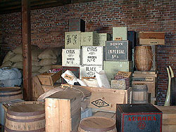 Piles of wooden crates, barrels, and other containers fill the public stores