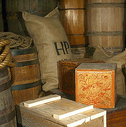 Boxes, bags, and barrels stacked in the Public Stores carried exotic goods