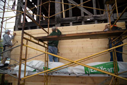 workmen on a scaffold attach sheathing to the frame of the building.