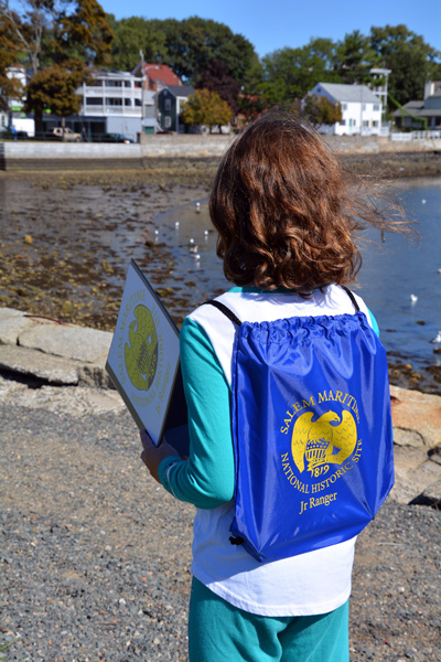 A young girl holds a Junior Ranger book and bag and looks at the ocean