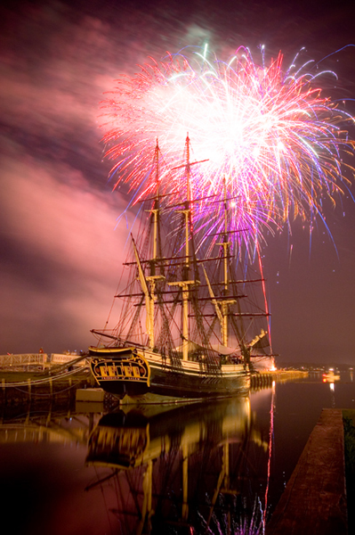 Fireworks explode behind the tall ship Friendship of Salem