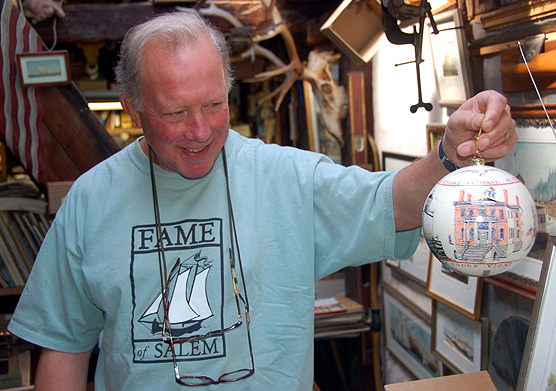 Salem artist Racket Shreve holding up a 6 inch diameter ornament decorated with buildings at Salem Maritime