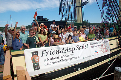 Volunteers and staff of Salem Maritime NHS wave from the deck of Friendship