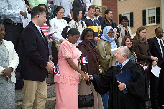 Judge Douglas Woodlock shakes hands with a new U.S. citizen