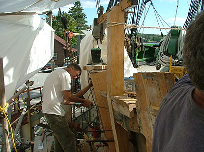 an oak upright timber at the front of the ship is being installed.