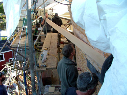Planking is dampened, fitted in place to match the curve of the hull, and fastened
