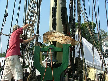 a volunteer removes the curved top to the belfry, which holds the ship's bell