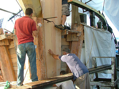 two men glueing a layer of wood onto the structural timbers on the front of the ship