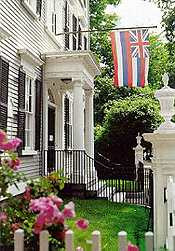 The front of the Stephen Phillips House, a gray three story building with black shutters and a white portico.  The Hawaiian flag hangs in front of the house.