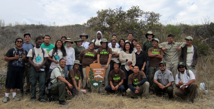 A group of young volunteers pose with a large National Park Service arrowhead