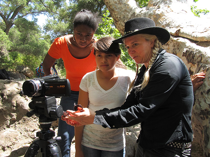 Artist in resident shows two young students how to use a video camera