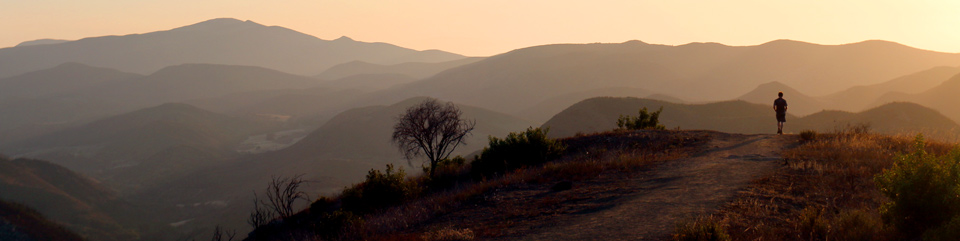 Mountain ridges recede into the distance while a lone hiker stands silhouetted on a trail at sunset