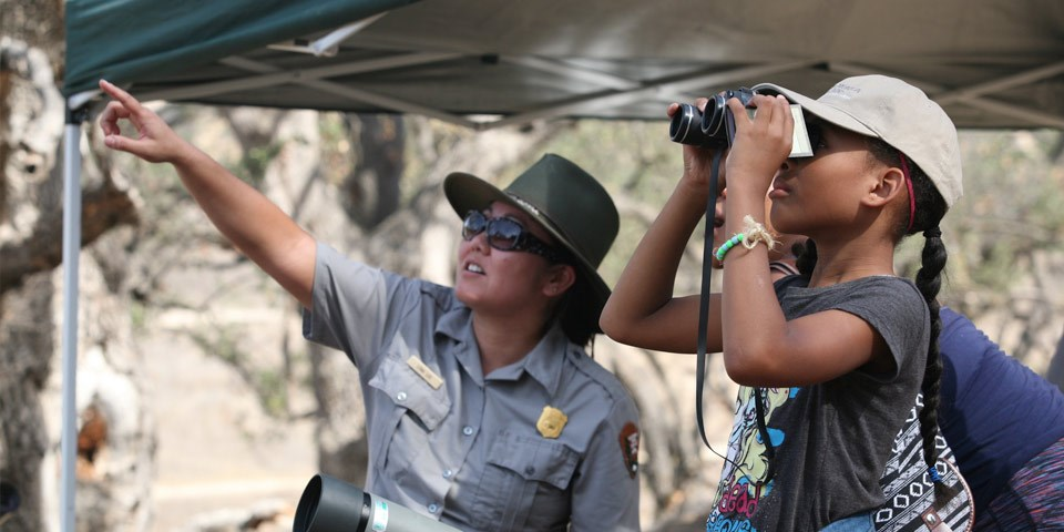 A ranger points off into the distance while a young visitor looks through binoculars