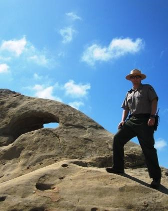 A park ranger stands next to an iconic rock formation at Castro Crest.