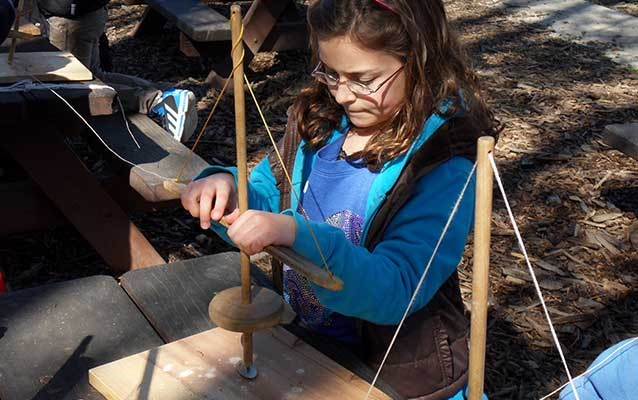 A student uses a hand drill to make a shell necklace