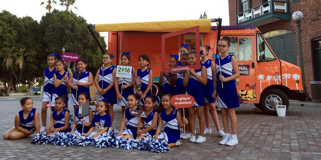 Cheerleading squad posing in front of the LA Ranger Troca.