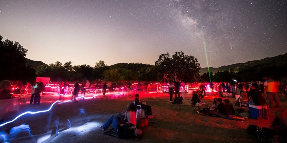 Visitors gaze at the night sky while laser pointers display constellations