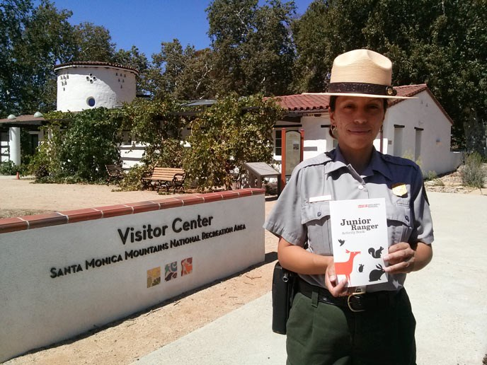A park ranger holds a small activity book and poses in front of the visitor center