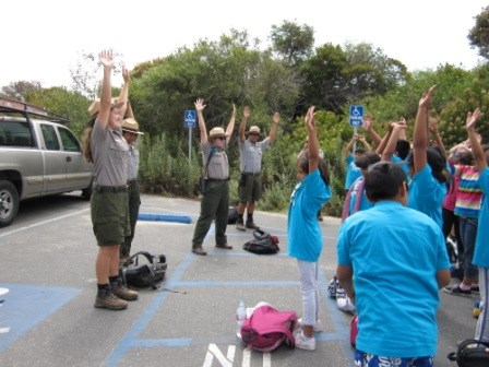 Students do stretching exercises  before a morning hike with National Park Service Rangers at Leo Carrillo State Beach.