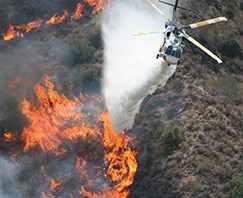 A fire helicopter drops water on a large fire.