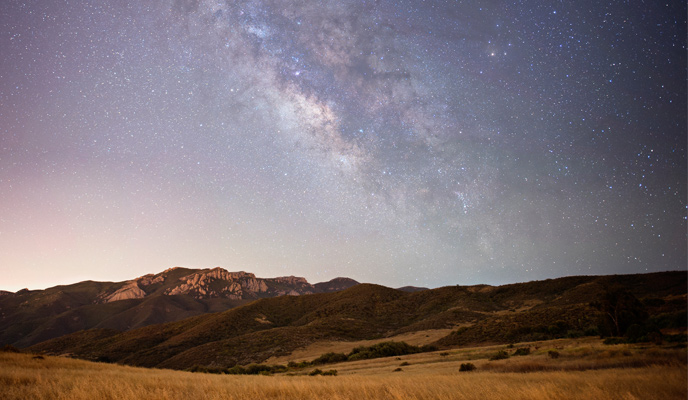A view of the Milky Way over mountain ridges and open grassland